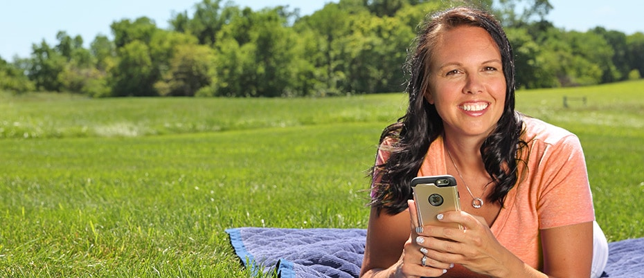 Woman on blanket outside with phone