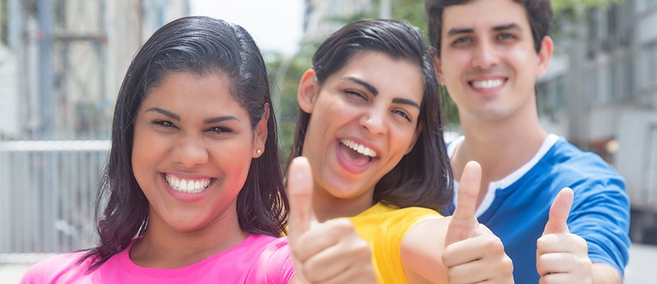 Three young people with thumbs up