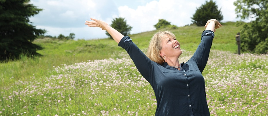 Woman loving nature with arms raised