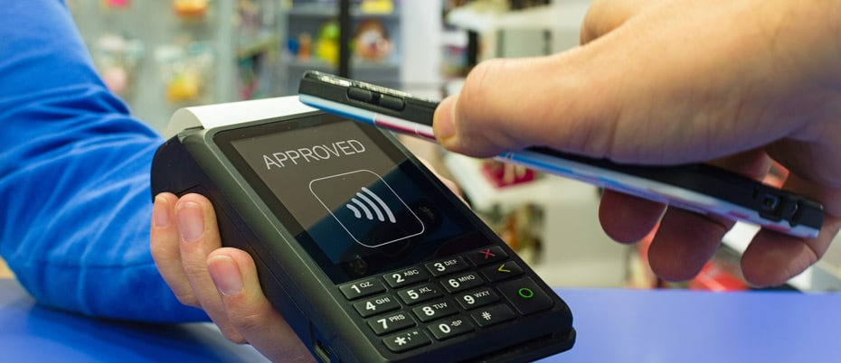 """Mobile phone poised over POS terminal that shows """"Approved"""" with regards to digital wallet payment"""