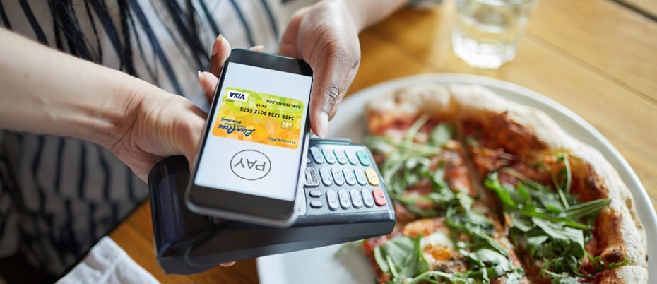 Mobile phone poised above pay terminal to pay with a digital wallet, pizza in background