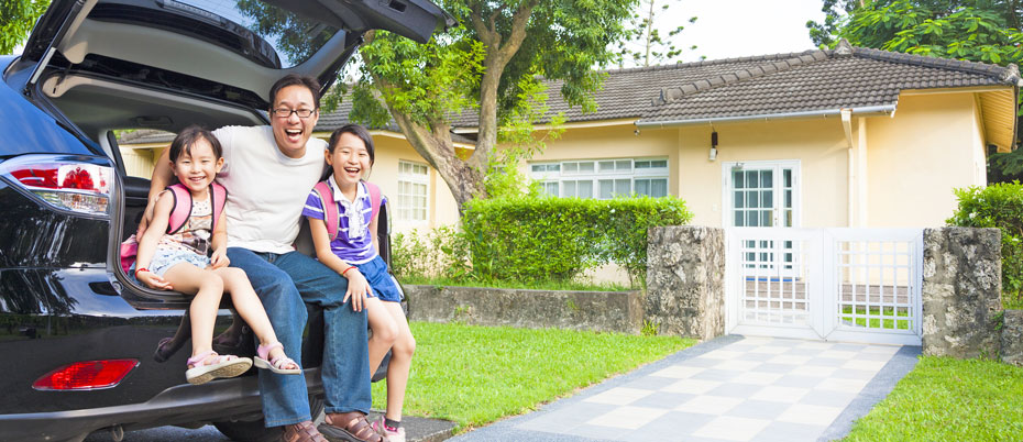 Family of three sits in car in front of home