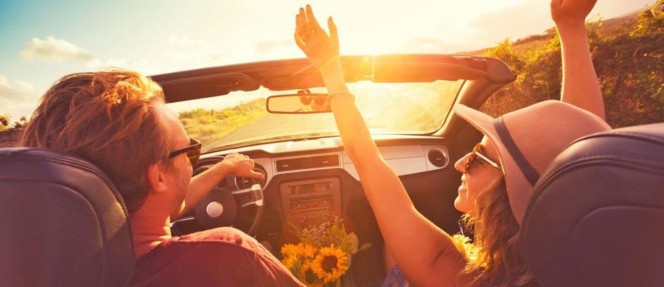 Man and woman enjoyin an evening drive in a convertible
