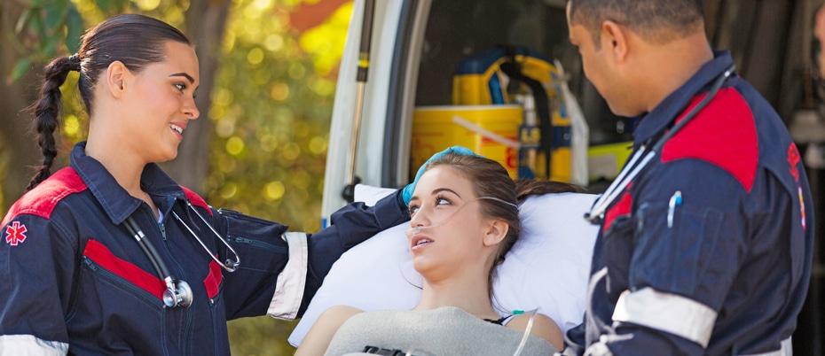 Paramedics reassuring a woman on a gurney