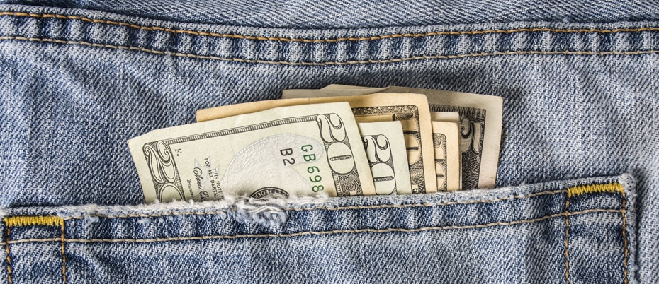 Bills sticking out of the back pocket of a pair of jeans