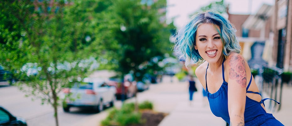 Young, attractive woman smiling in front of Cedar Rapids cityscape