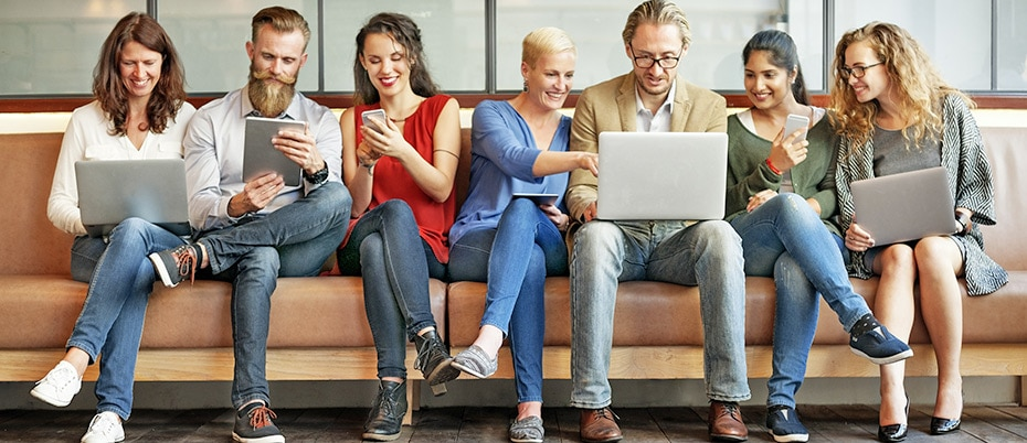 Connected people sitting on bench using mobile devices and laptops