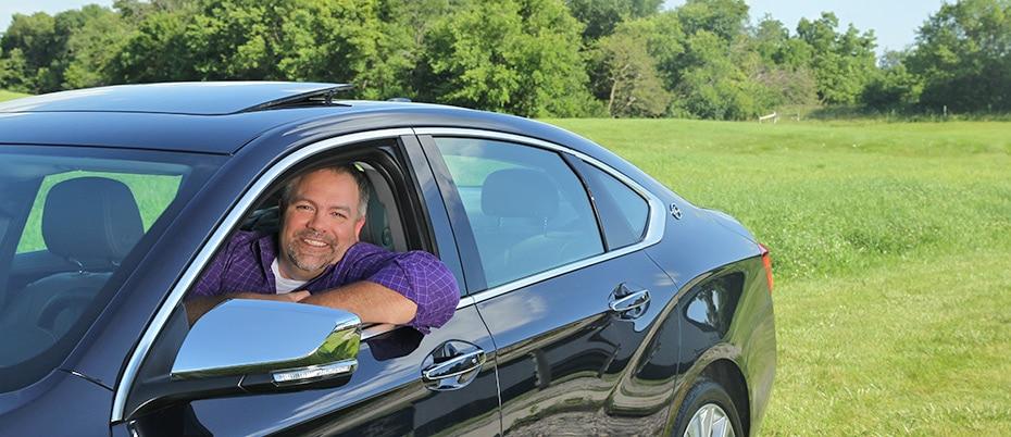 Happy man in shiny new car