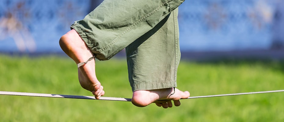 Barefoot man balances on slackline