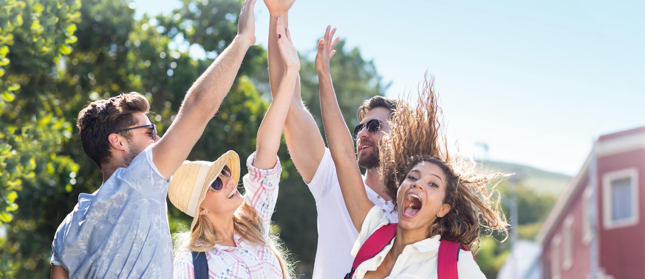 Four friends high-five outdoors