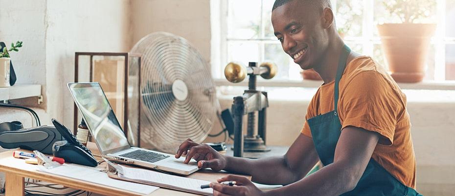 Male craftsman does bookwork on laptop