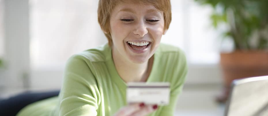 Young woman smiles at credit card