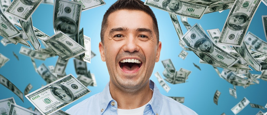 Happy man with money falling all around