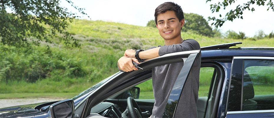 Young man standing next to a car with key in his hand