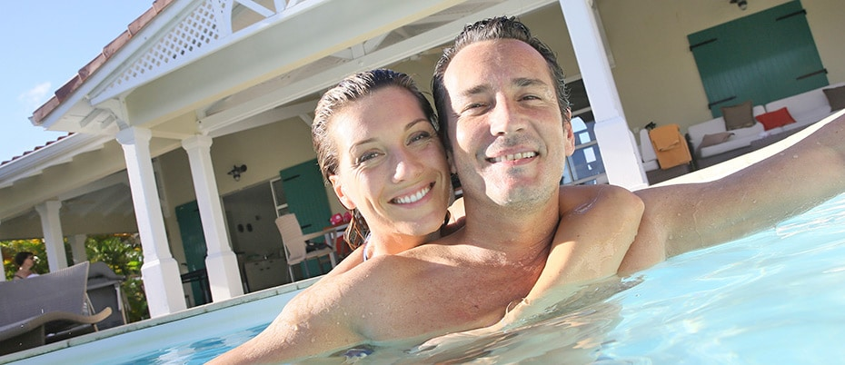 Couple embrace in pool at home