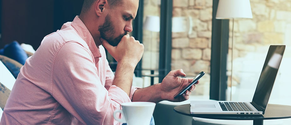 Man in coffee shop checks mobile devices