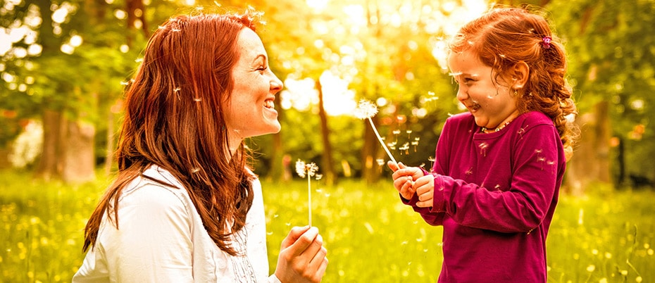 Mom and daughter blowing on dandelions
