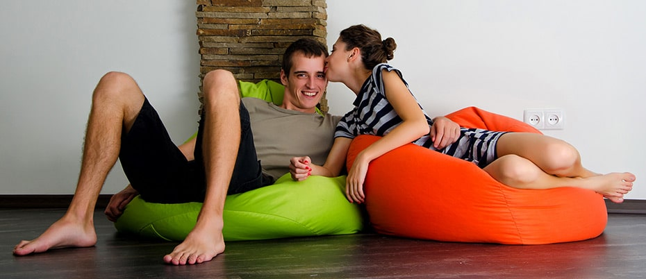 Young couple in bean bag chairs