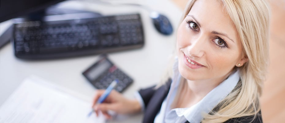 Businesswoman looking up from keyboard, paperwork, and calculator