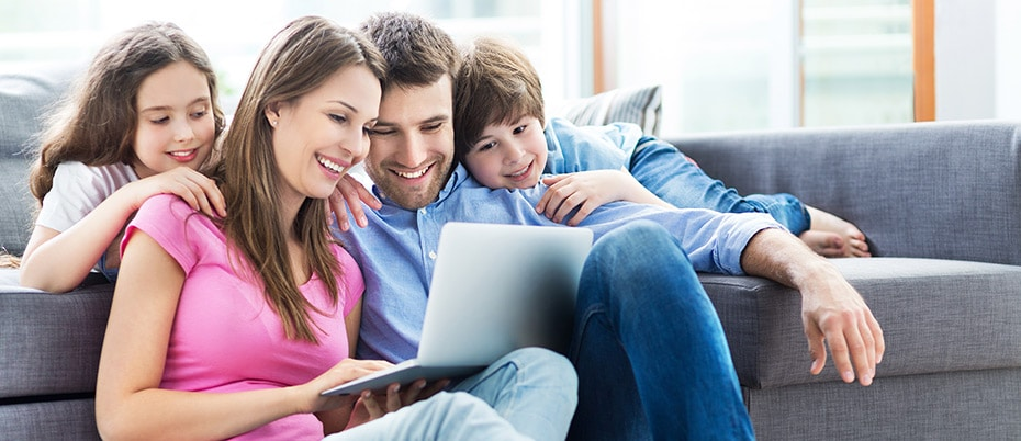 Family on sofa looking at laptop together