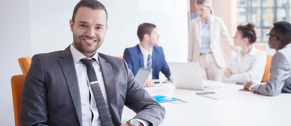 Young man in grey business suit smiling at conference table