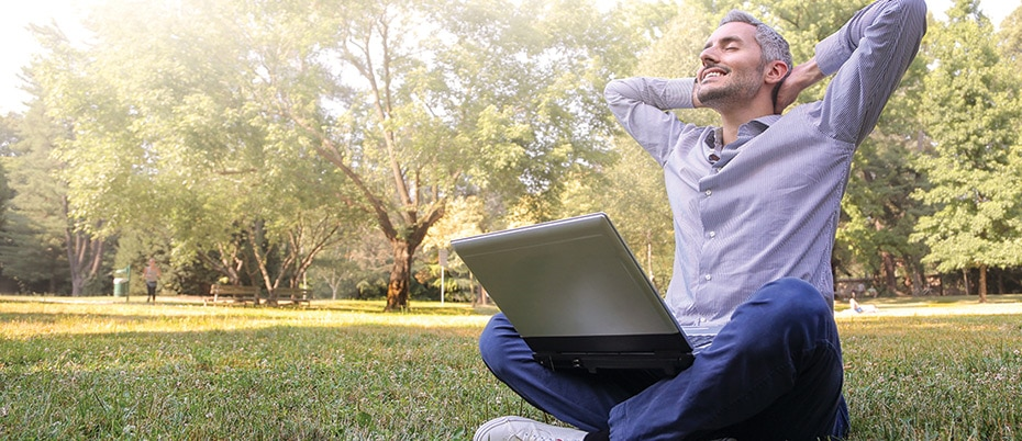 Relaxed man in park with laptop