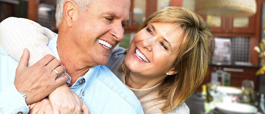 Older woman hugging husband and smiling