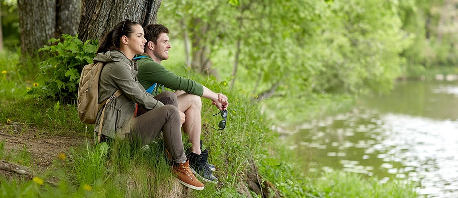 Young couple sitting on river bank
