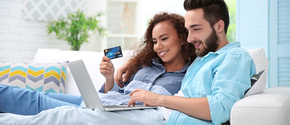 Couple on sofa using credit card online