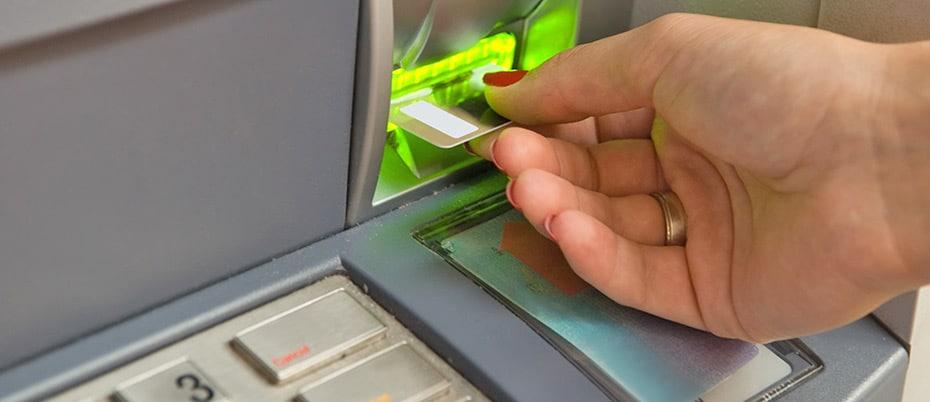 Woman's hand using ATM machine