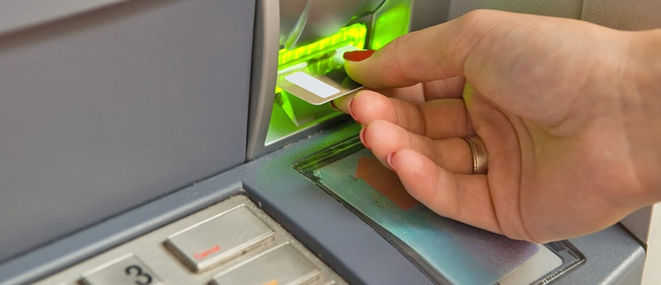 Woman's hand using ATM machine