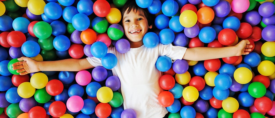 Smiling boy lays in ball pit