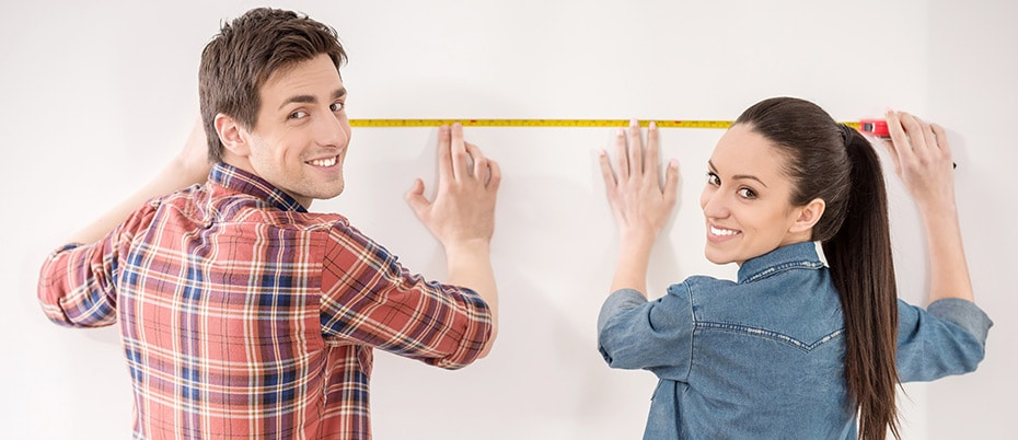 Young couple measure wall