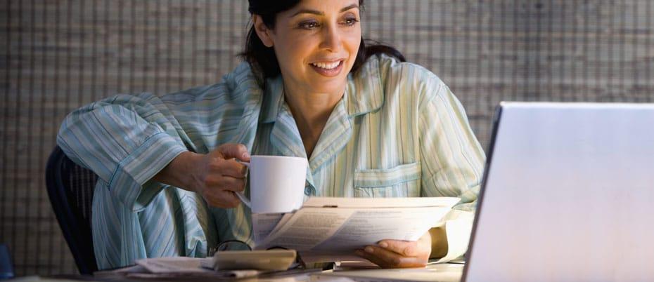Woman in pajamas pays bills on laptop