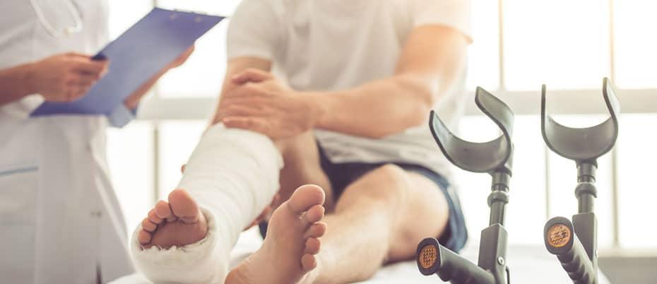Doctor talks to man with broken leg