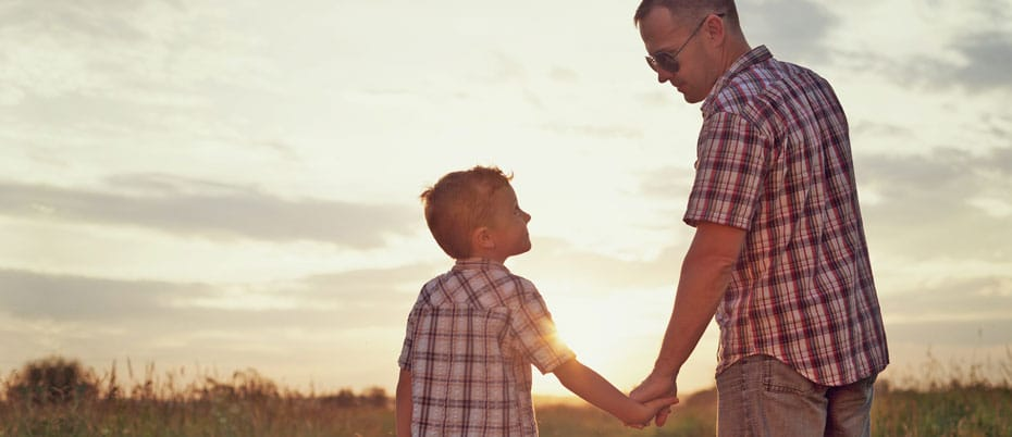 Dad and son holds hands at sunset