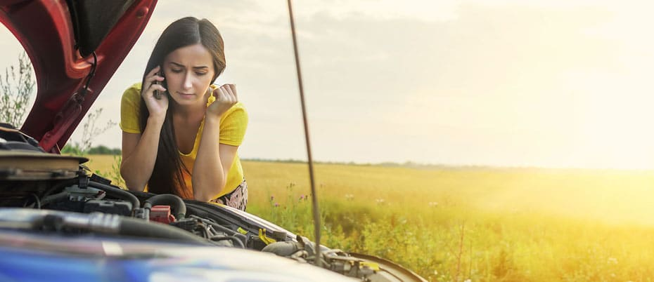 Girl on phone leans on broken-down car