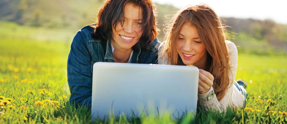 Mom & daughter lying in grass with laptop