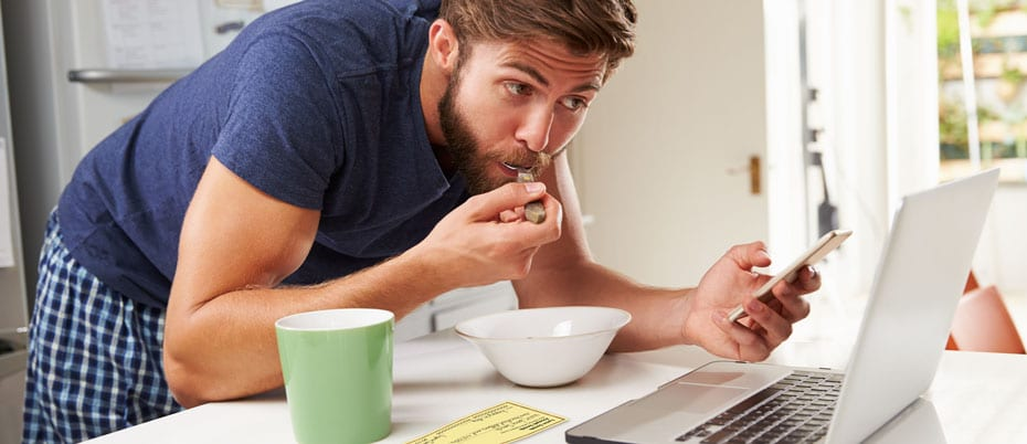 Man eats cereal, checks phone while online