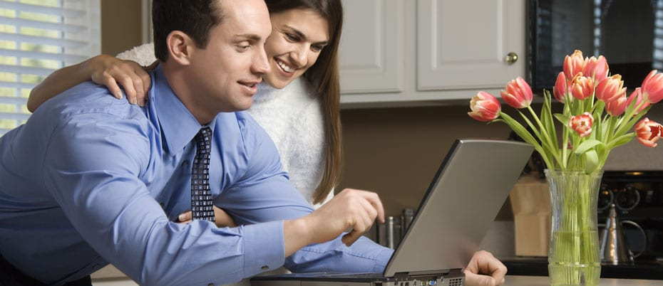 Young couple in kitchen look at laptop