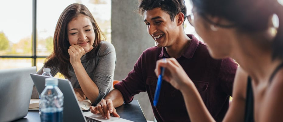 Three smiling students look at laptop