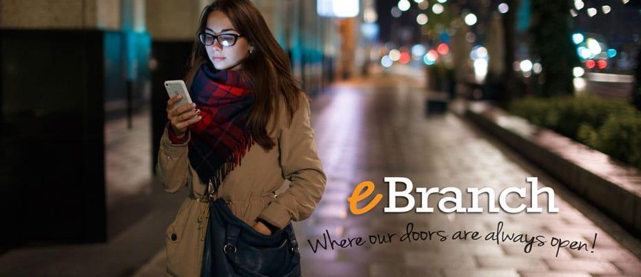 Girl checking mobile phone at night on city sidewalk