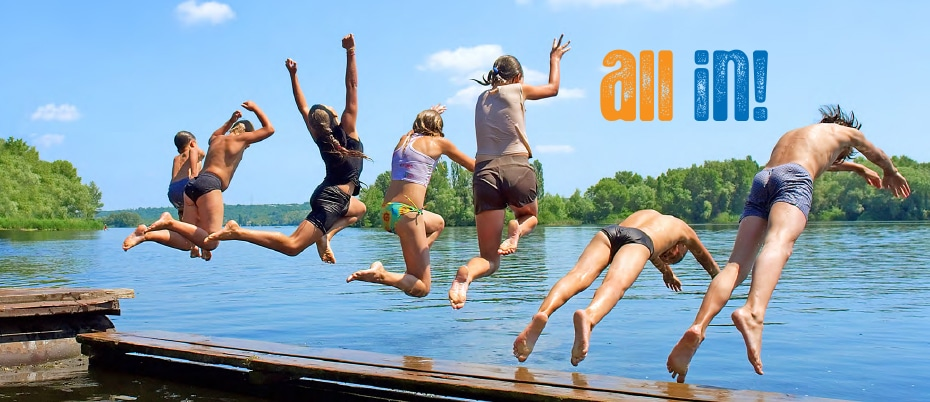People in swimsuits jumping off a dock into water