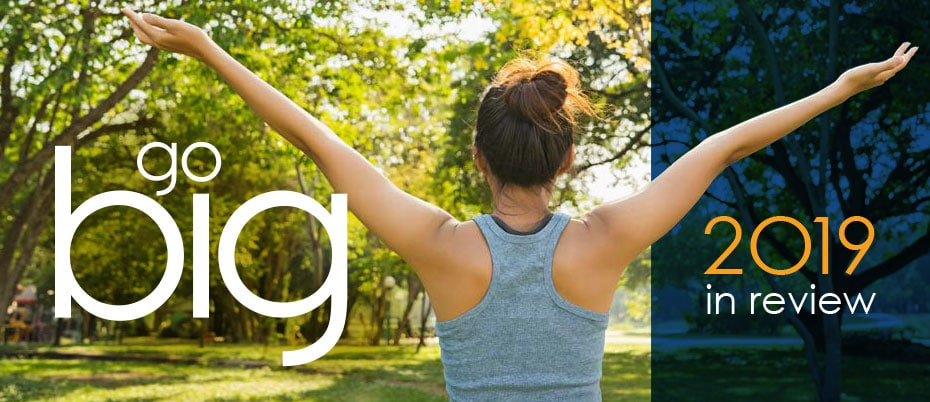Woman standing in a park with her arms outstretched. Text: Go big, 2019 in review