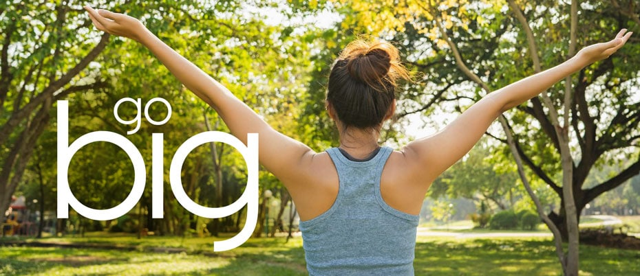 Woman with her back to us in park, arms raised wide
