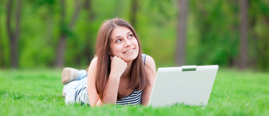 Dreamy girl lying in the grass in park with laptop