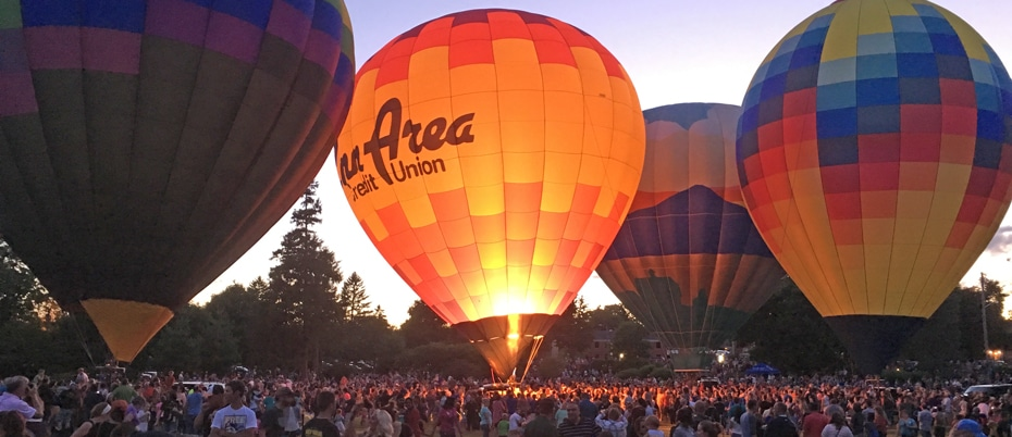 Four colorful hot-air balloons with crowd at Balloon Glow