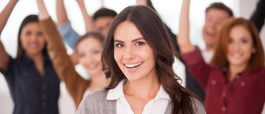 Smiling woman in front of cheering employees
