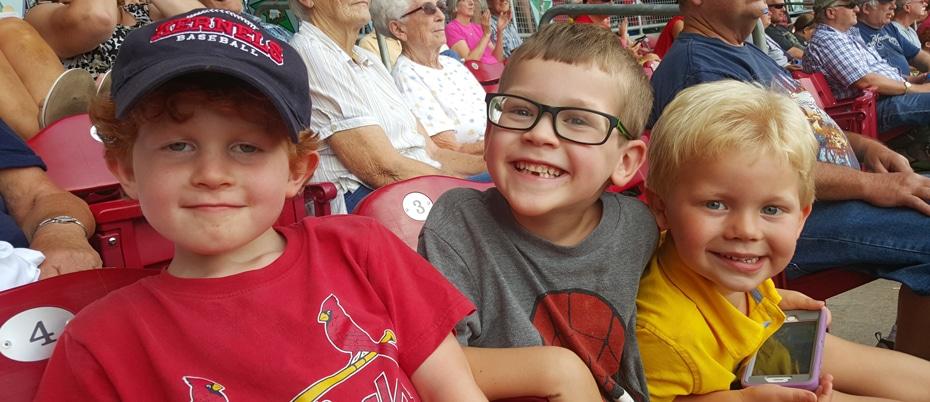 Three young boys at baseball game