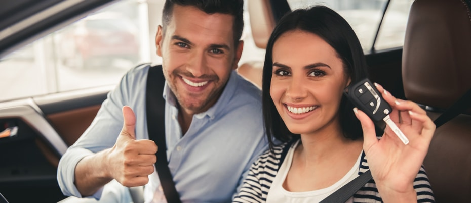 Happy man and woman in a new car holding up keys